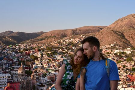Couple on the viewpoint in Guanajuato. Young man and woman leaning on his shoulder and historical downtown and colonial arhitecture on the hills behind them. Travelling together, discovering world while being in love. Zdjęcie Seryjne