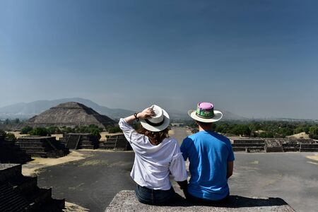 Couple sitting on Pyramid of the Moon and overlooking Road of the Dead and Pyramid of the Sun in Teotihuacan - travel destination in Mexico.