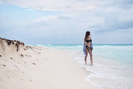 Young woman standing in the tide at the coast. Sea water washes over her feet, female looking to horizon. Solitude and relaxation during tropical vacation in summertime.