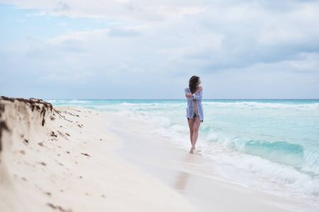 Female walking along sandy beach. Young beautiful lady watching over horizon and enjoying hew relaxing solitude during her trip to tropical destination for vacations.