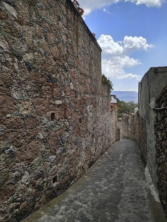 Steap street going downhill with old grunge walls on both sides - colonial style in Mexico. Travel and architectural background with nobody in frame.