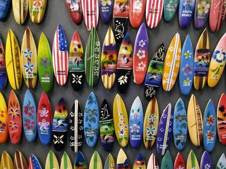 Various numerous surfboard shaped wooden handmade magnets on the wall. Little souveniers from South Beach in Miami. Travel and touristic background Zdjęcie Seryjne