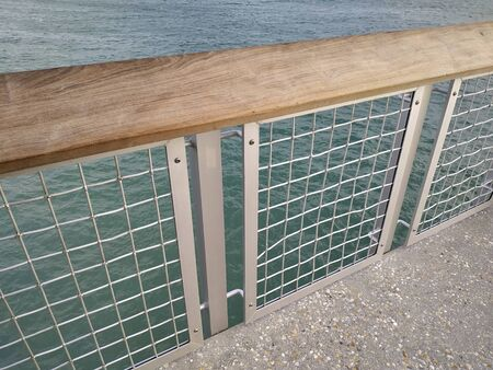 Fence on a concrete pier to protect the edge of construction and visitors. Blue sea waters behind it. Cage and bars for security of human beings.