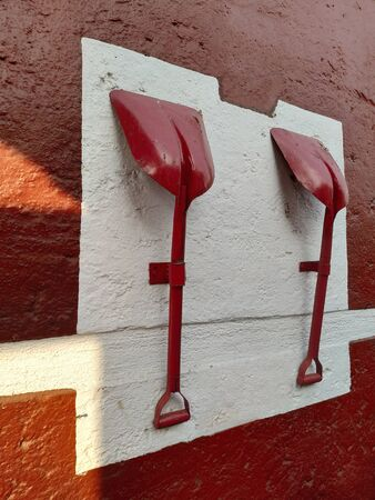 Red shovels for sand handing on the wall of a fire station