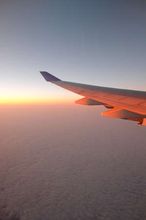 nimbi: Airplane Wing in Flight from window with sunset Stock Photo