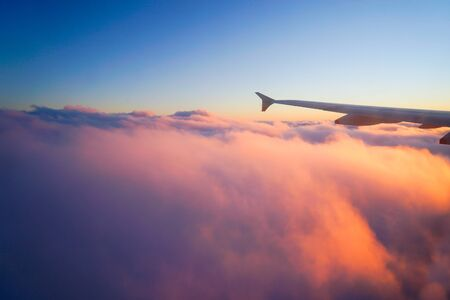 flight: Airplane Wing in Flight from window, sunset sky