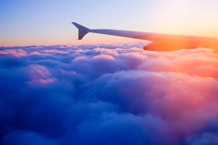Ala del aeroplano en vuelo desde la ventana, el cielo del atardecer Foto de archivo - 42666934