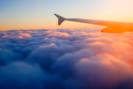 flucht: Flugzeugflügel im Flug aus dem Fenster, Sonnenuntergang Himmel Lizenzfreie Bilder