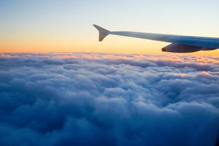 ウィンドウ、夕焼け空から飛行中の飛行機の翼