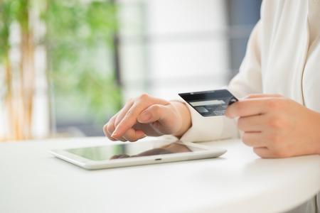 Handen van een kantoor vrouw te typen toetsenbord met creditcard