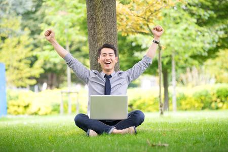 公園でタブレット、ノート パソコン、携帯電話を使用してアジア ・成功の青年実業家