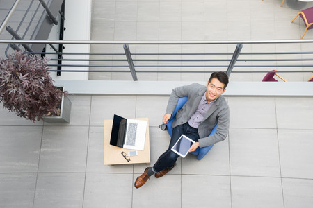 Young asian businessman using tablet, mobile phone in the office 스톡 콘텐츠