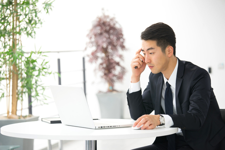 asian style: Young asian businessman using tablet, mobile phone in the office Stock Photo