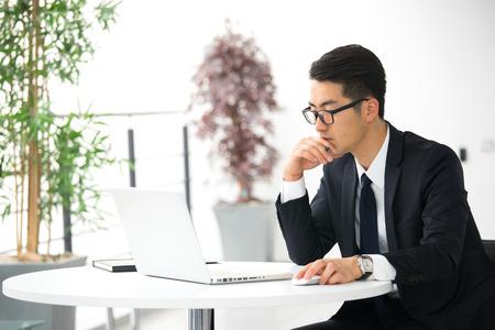 Jonge Aziatische zakenman met behulp van tablet, mobiele telefoon in het kantoor Stockfoto