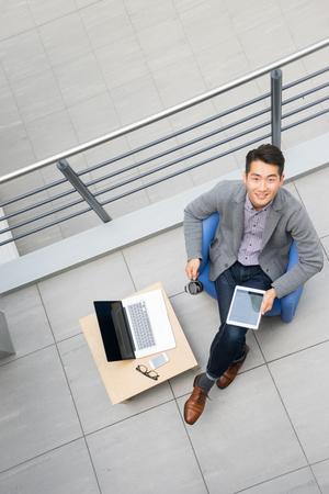 Jonge Aziatische zakenman die tablet, mobiele telefoon in het bureau gebruiken Stockfoto - 44151403