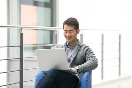 Young asian businessman using tablet, mobile phone in the office Banque d'images