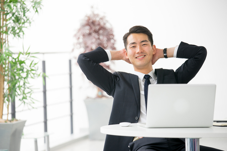タブレット、オフィスで携帯電話を使用して若いアジア系のビジネスマン