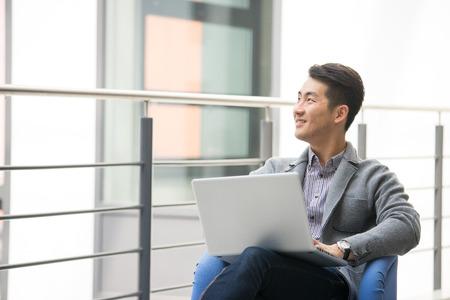 Jonge Aziatische zakenman die tablet, mobiele telefoon in het bureau gebruiken