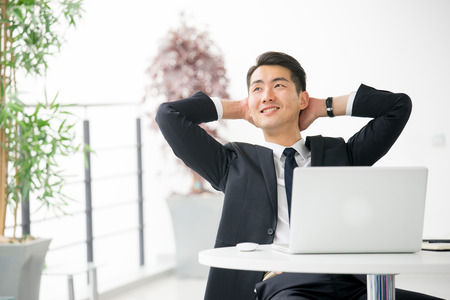office break: Young asian businessman using tablet, mobile phone in the office Stock Photo