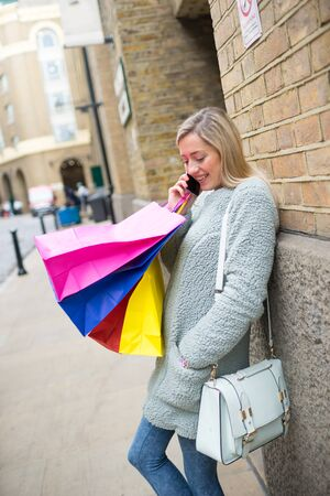 gift spending: A beautiful woman with shopping bags in shopping street, London
