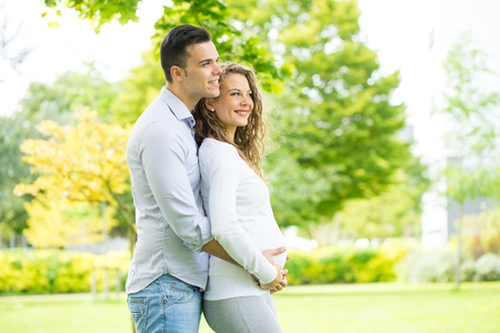 marido y mujer: Feliz pareja embarazada y j�venes en el parque en verano Foto de archivo