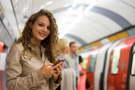 Een vrouw met behulp van een mobiele telefoon op de buis metrostation, Londen