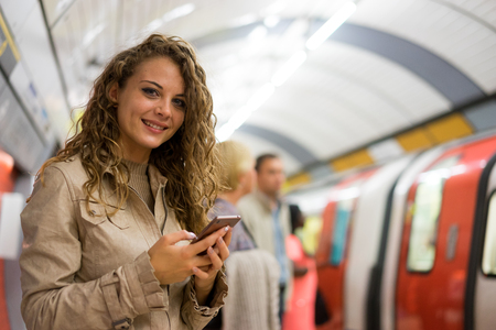A woman using a mobile phone on the tube underground station, London Foto de archivo