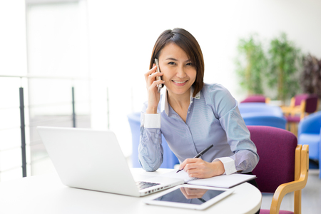 at her desk: Asian Businesswoman sitting at her desk in an office Stock Photo