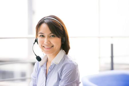 call centre girl: Asian Business woman talking using her headset in the office Stock Photo