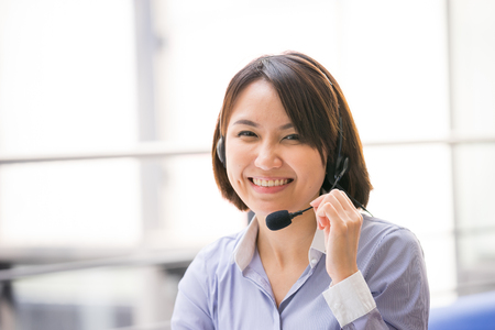 business services: Asian Business woman talking using her headset in the office Stock Photo