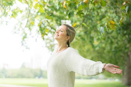 Feliz y concepto de la libertad, la mujer en el parque al aire libre