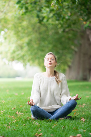 lotus pose: Young woman meditating and Yoga in a park
