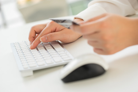 shopping online: Hands of an office woman typing keyboard with credit card
