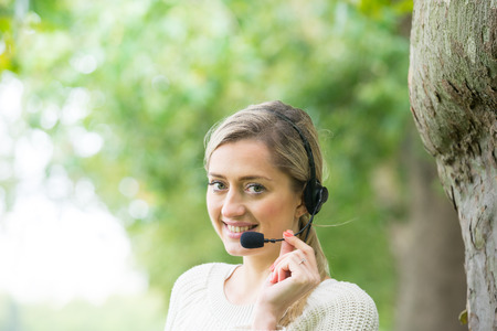 handsfree telephone: Business woman talking using her headset in the park