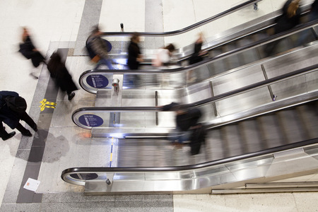 london people: Blur Movement Business people walking on escalator in Rush Hour train station, London, UK