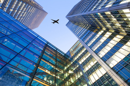 A jet airplane silhouette with business office towers background