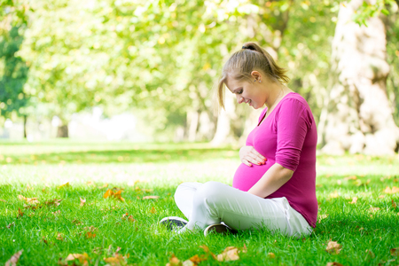 Happy and young pregnant woman in park in summer Stock Photo