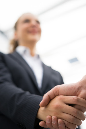 partnership power: Business man and woman handshake at office