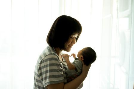 Asia madre sostiene a su bebé recién nacido