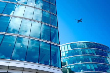 exterior architecture: A jet airplane silhouette with business office towers background, London