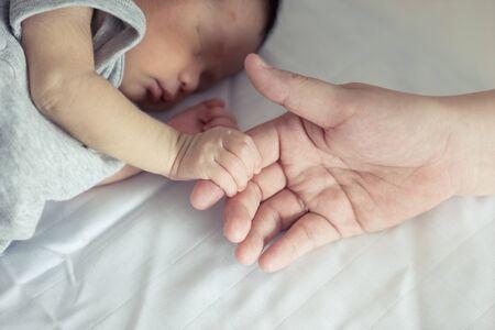 recien nacido: Asia madre sostiene a su bebé recién nacido