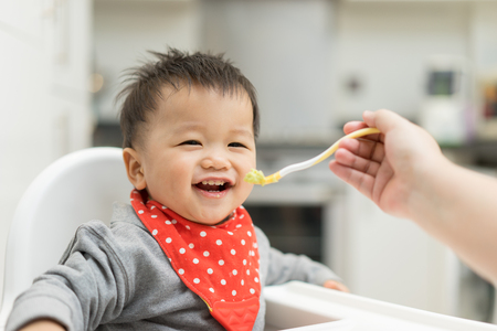 Asian baby boy eating blend food on a high chair 스톡 콘텐츠