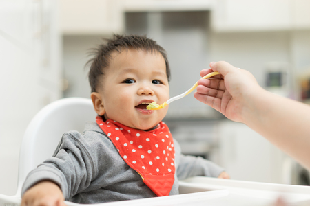 Asian baby boy eating blend food on a high chair Stock Photo