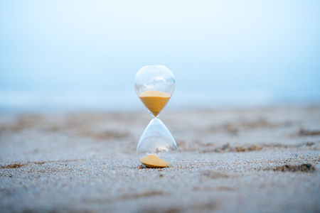 Sand clock on the beach, business time management concept Imagens