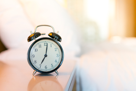 Metal Alarm clock on white bedroom Stock Photo