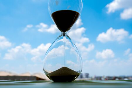 Sand clock with sky and cloud business concept