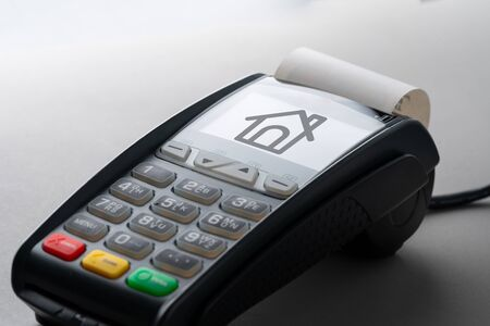 House icon on credit card machine for property concept