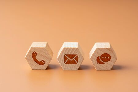 Contact us icon on wood puzzle with hand