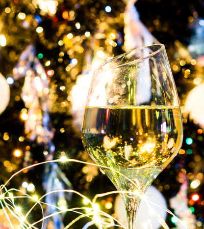 White wine or champagne in front of Christmas tree with yellow lights Stock Photo