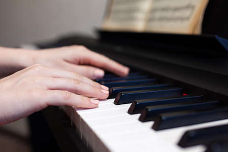 Woman hand's playing on the piano close up detail